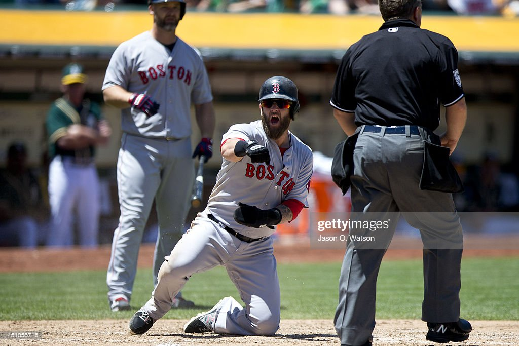 Mike Napoli of the Boston Red Sox celebrates after stealing home plate against the Oakland Athletics during the third inning at Oco Coliseum on June...