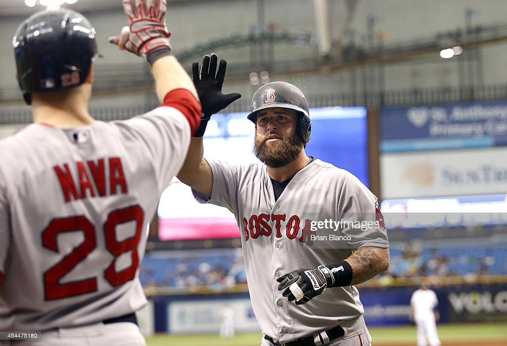 Mike Napoli of the Boston Red Sox celebrates his solo home run with teammate Daniel Nava during the fourth inning of a game against the Tampa Bay...