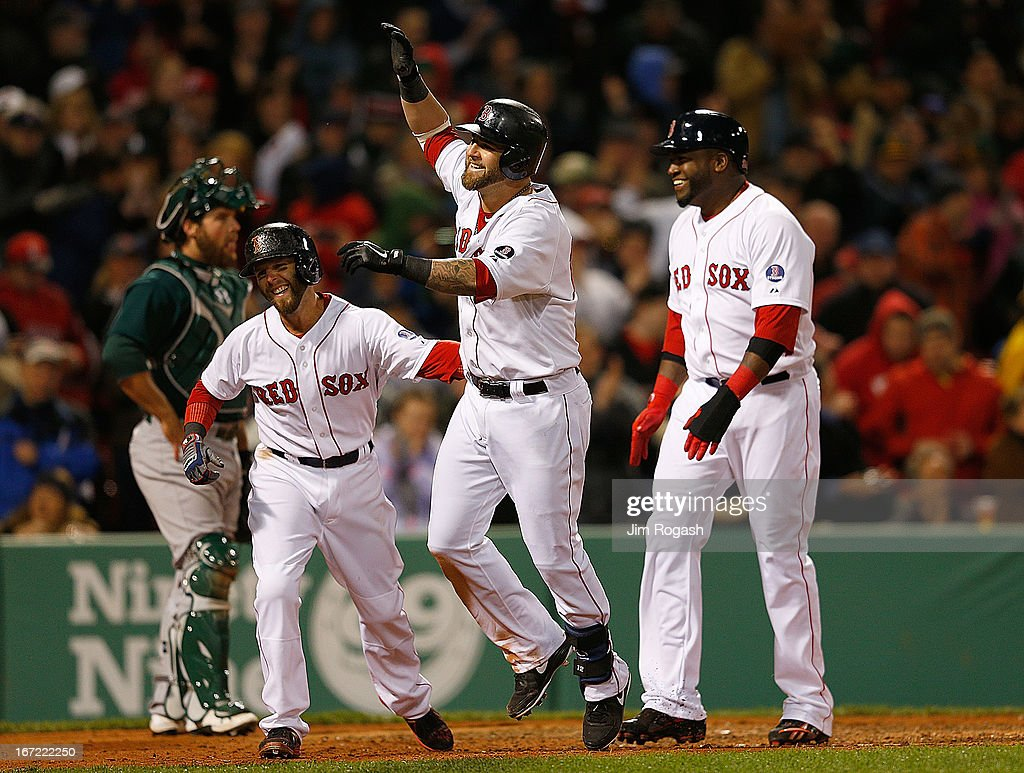 Mike Napoli #12 of the Boston Red Sox celebrates with David Ortiz #34 and Dustin Pedroia #15 after Napoli connected for a grand slam in the fifth inning against the Oakland Athletics at Fenway Park on April 22, 2013 in Boston, Massachusetts.