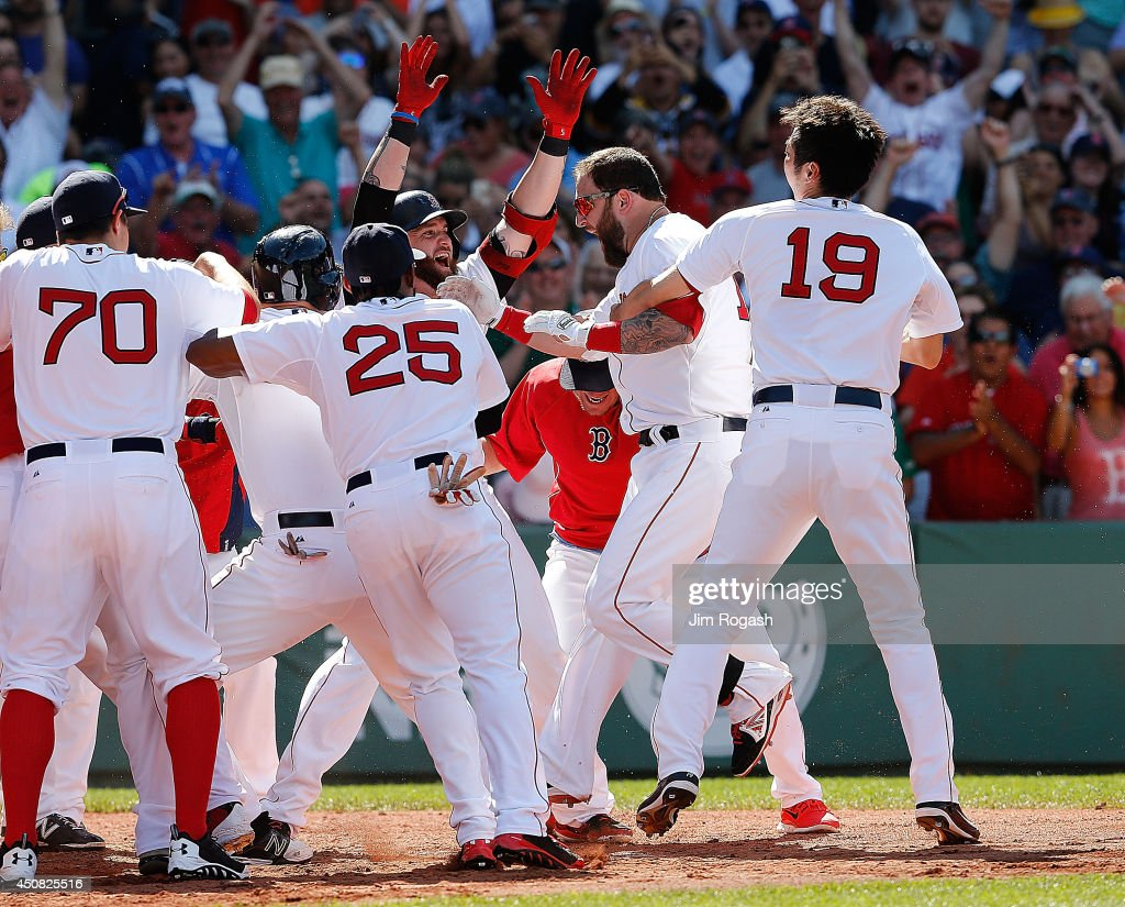 Mike Napoli #12 of the Boston Red Sox celebrates with teammates after connected for a game-winning walk off home run against Minnesota Twins in the 10th inning at Fenway Park on June 18, 2014 in Boston, Massachusetts. (Photo by Jim Rogash/Getty Images)2