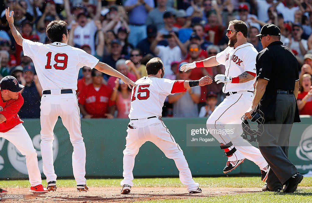 Mike Napoli of the Boston Red Sox celebrates with teammates after connected for a gamewinning walk off home run against Minnesota Twins in the 10th...