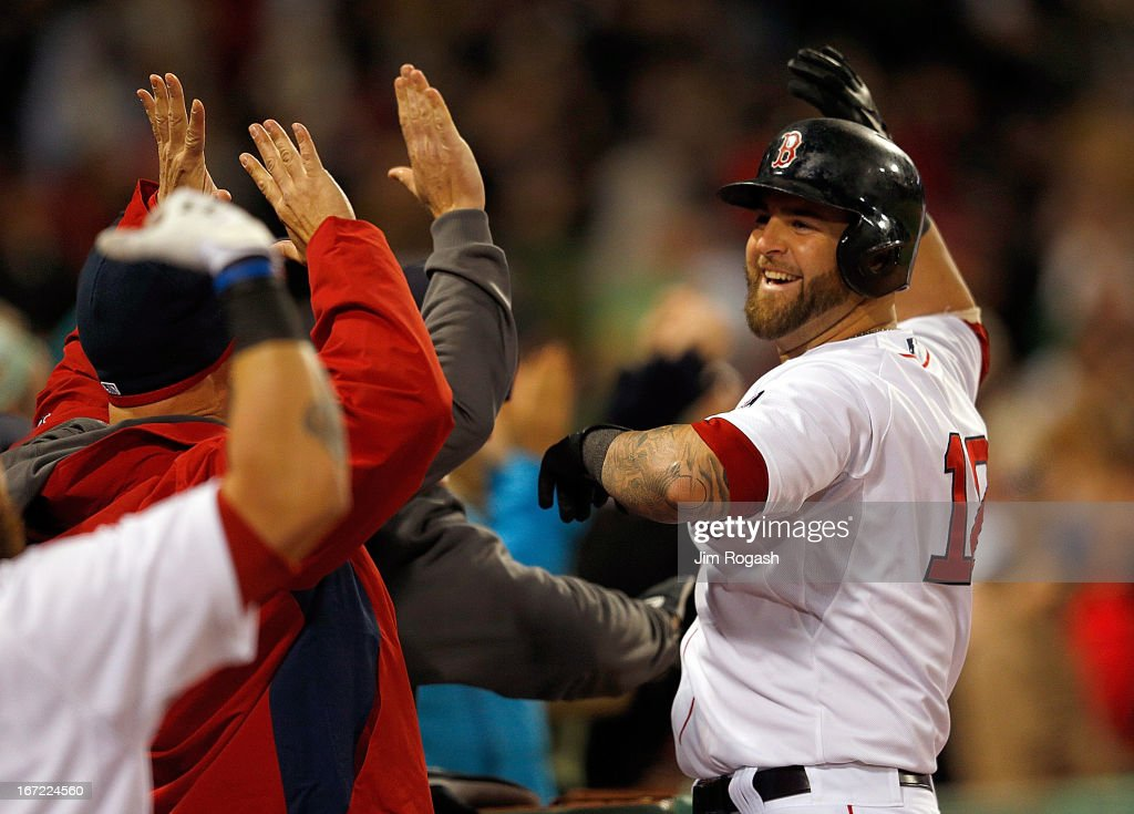 Mike Napoli #12 of the Boston Red Sox celebrates with teammates after he connected for a grand slam in the fifth inning against the Oakland Athletics at Fenway Park on April 22, 2013 in Boston, Massachusetts.