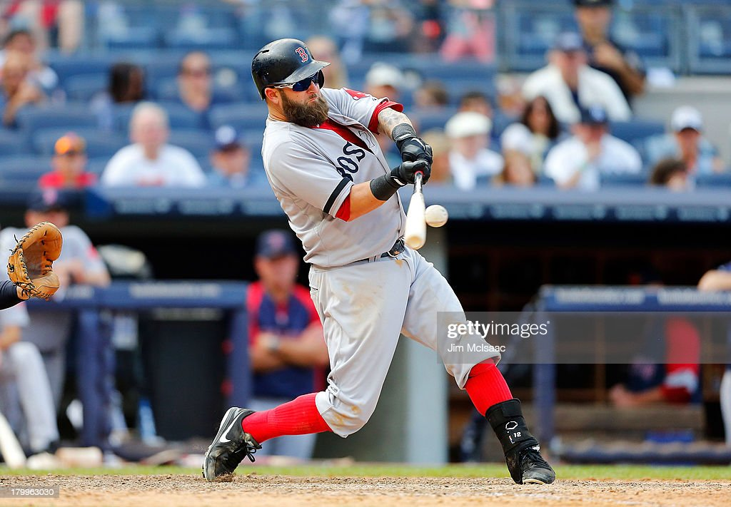 Mike Napoli #12 of the Boston Red Sox connects on a ninth inning home run against the New York Yankees at Yankee Stadium on September 7, 2013 in the Bronx borough of New York City.