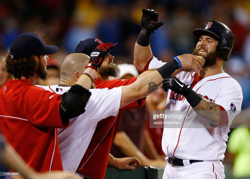 Mike Napoli of the Boston Red Sox has his beard pulled in celebration by his teammates in the dugout after scoring against the Detroit Tigers during...