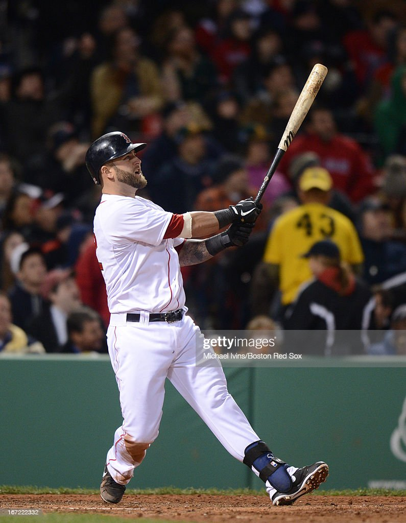 Mike Napoli #12 of the Boston Red Sox hits a grand slam home run against the Oakland Athletics in the fifth inning on April 22, 2013 at Fenway Park in Boston, Massachusetts.
