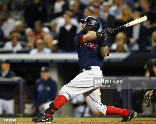 Mike Napoli of the Boston Red Sox hits a grand slam home run in the seventh inning against the New York Yankees in an MLB baseball game at Yankee...