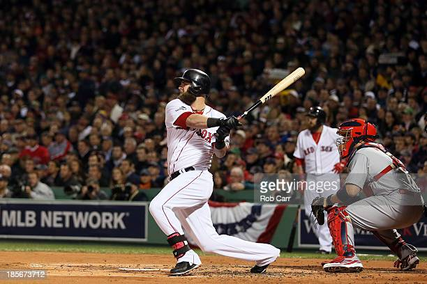 Mike Napoli of the Boston Red Sox hits a three run double in the first inning against the St Louis Cardinals during Game One of the 2013 World Series...