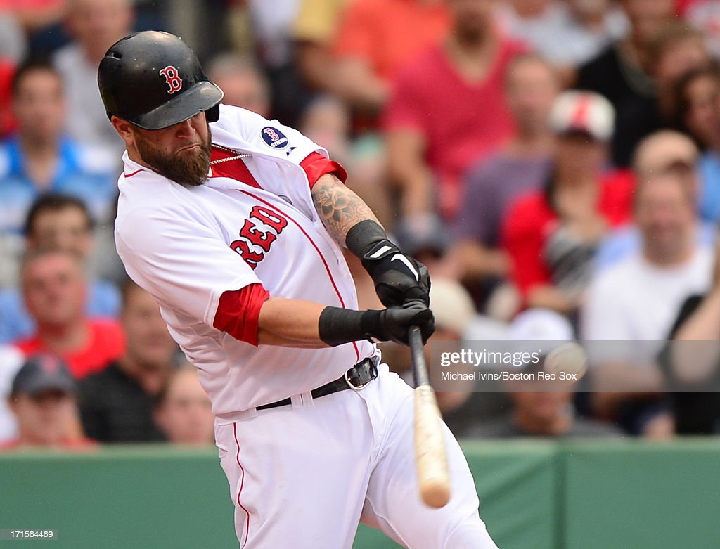 Mike Napoli #12 of the Boston Red Sox hits an RBI single against the Colorado Rockies in the third inning on June 26, 2013 at Fenway Park in Boston, Massachusetts.