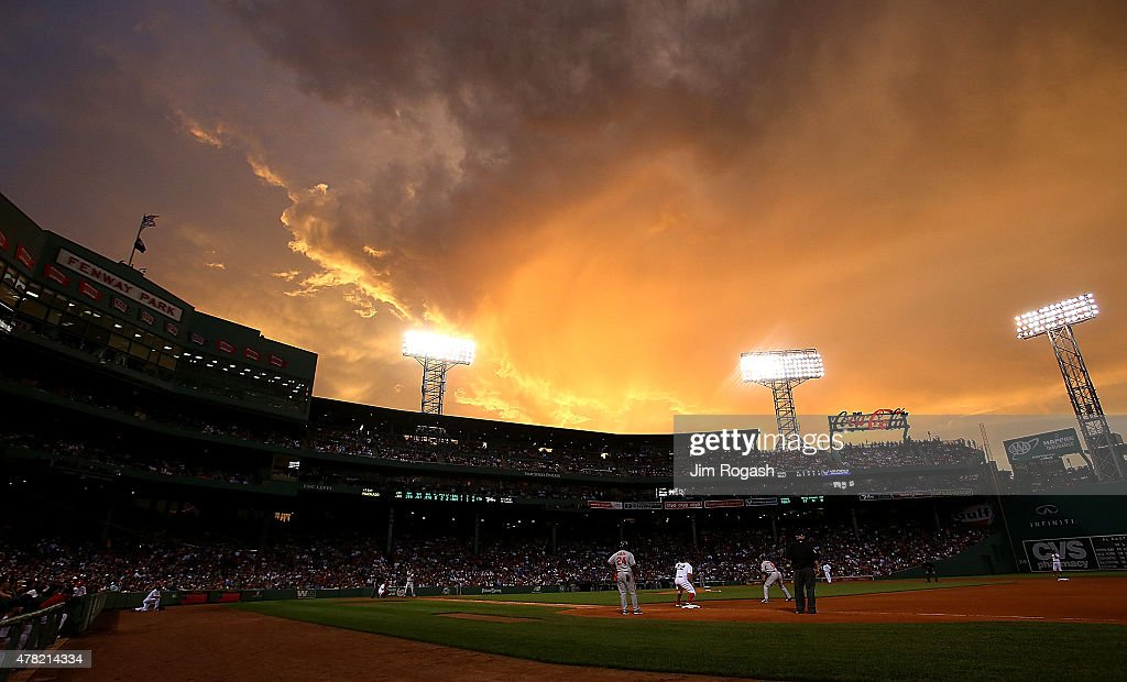 Mike Napoli of the Boston Red Sox holds David Lough of the Baltimore Orioles at first base in the fourth inning at Fenway Park on June 23 2015 in...