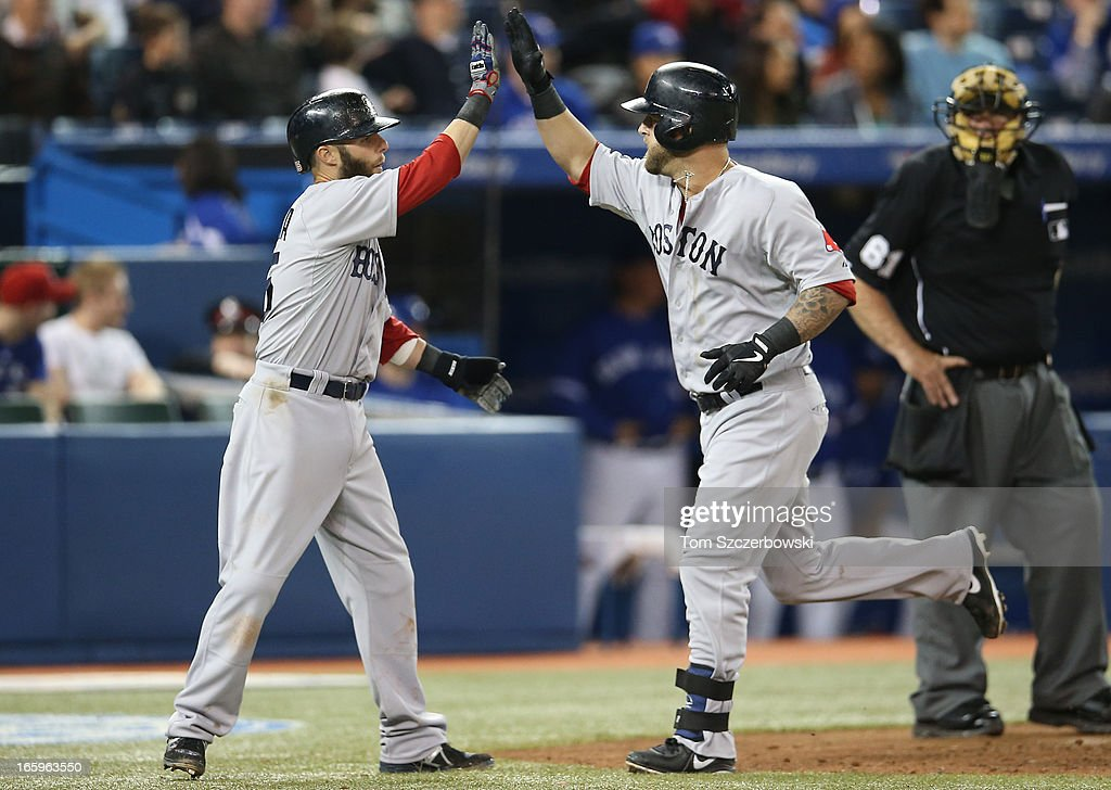 Mike Napoli #12 of the Boston Red Sox is congratulated by Dustin Pedroia #15 after hitting a 2-run home run in the eighth inning during MLB game action against the Toronto Blue Jays on April 7, 2013 at Rogers Centre in Toronto, Ontario, Canada.