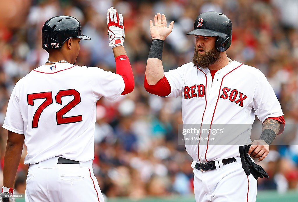 Mike Napoli #12 of the Boston Red Sox is congratulated by teammate Xander Bogaerts #72 of the Boston Red Sox after scoring in the second inning against the New York Yankees during the game on September 14, 2013 at Fenway Park in Boston, Massachusetts.