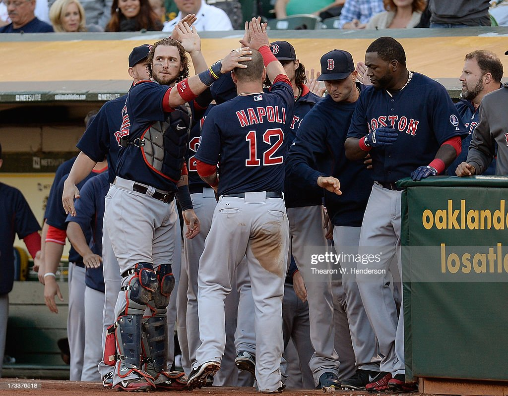 Mike Napoli #12 of the Boston Red Sox is congratulated by teammates after scoring in the second inning against the Oakland Athletics at O.co Coliseum on July 12, 2013 in Oakland, California.