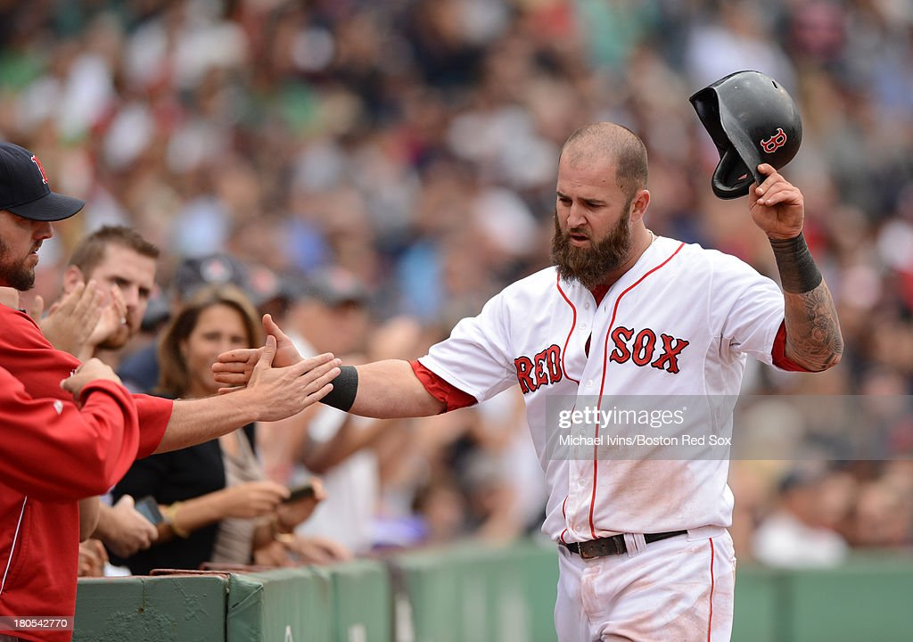 Mike Napoli #12 of the Boston Red Sox is congratulated by teammates after scoring against the New York Yankees during the fifth inning on September 14, 2013 at Fenway Park in Boston Massachusetts.
