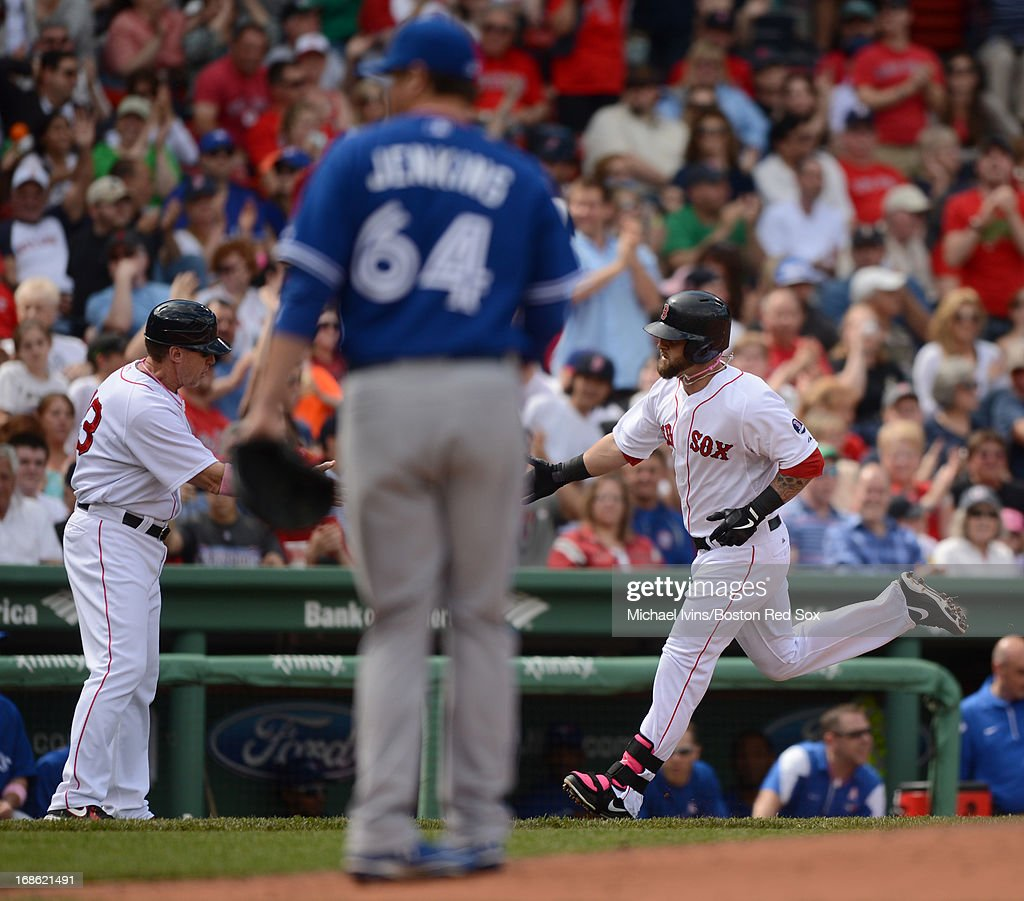 Mike Napoli #12 of the Boston Red Sox is congratulated by third base coach Brian Butterfield #13 after hitting a home run against Chad Jenkins #64 of the Toronto Blue Jays in the fourth inning on May 12, 2013 at Fenway Park in Boston, Massachusetts.
