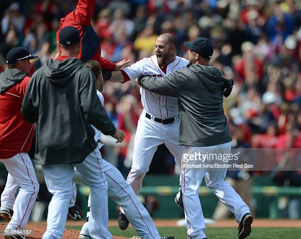Mike Napoli of the Boston Red Sox is mobbed by his teammates after hitting a walkoff RBI against the Tampa Bay Rays in the ninth inning on April 15...