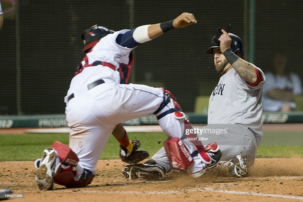 Mike Napoli #12 of the Boston Red Sox scores ahead of the tag by catcher Carlos Santana #41 of the Cleveland Indians in the seventh inning at Progressive Field on April 18, 2013 in Cleveland, Ohio.