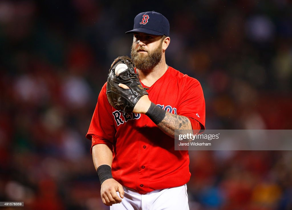 Mike Napoli of the Boston Red Sox shows the caught ball from a line drive that is stuck in his glove against the Detroit Tigers during the game at...