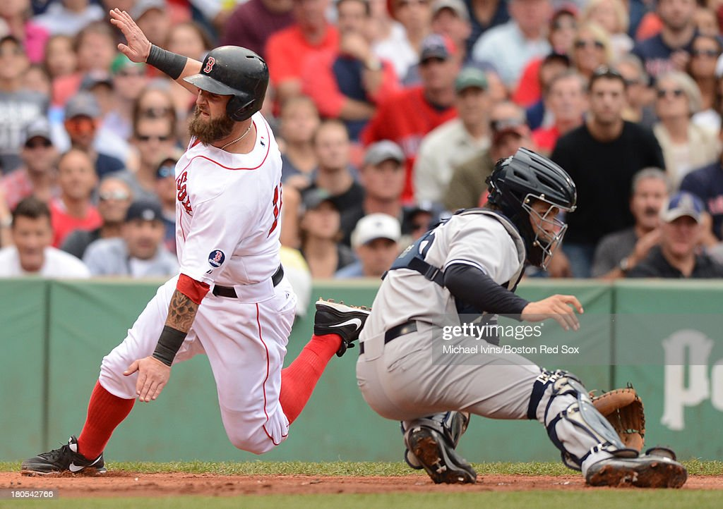 Mike Napoli #12 of the Boston Red Sox slides around J.R. Murphy #66 of the New York Yankees during the fifth inning on September 14, 2013 at Fenway Park in Boston Massachusetts.