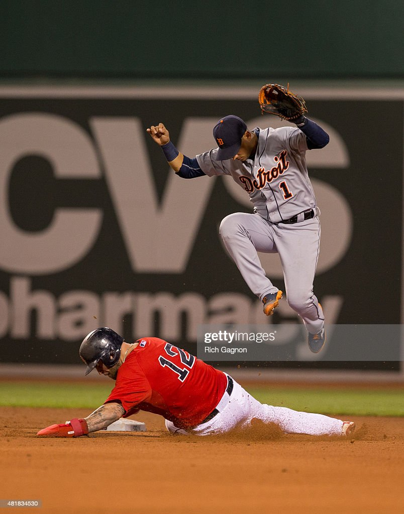 Mike Napoli #12 of the Boston Red Sox slides into Jose Iglesias #1 of the Detroit Tigers as Iglesias turns a double play on a ball hit by Alejandro De Aza during the fourth inning at Fenway Park on July 24, 2015 in Boston, Massachusetts.