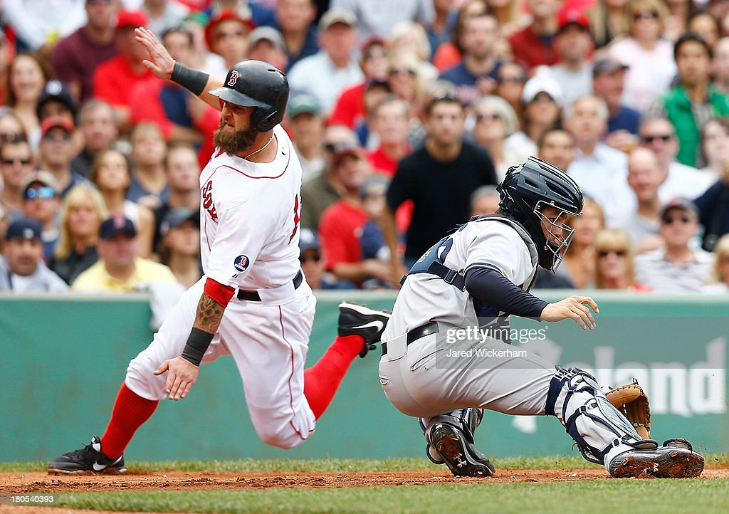 Mike Napoli #12 of the Boston Red Sox slides safely into home plate past J.R. Murphy #66 of the New York Yankees in the 5th inning to score during the game on September 14, 2013 at Fenway Park in Boston, Massachusetts.