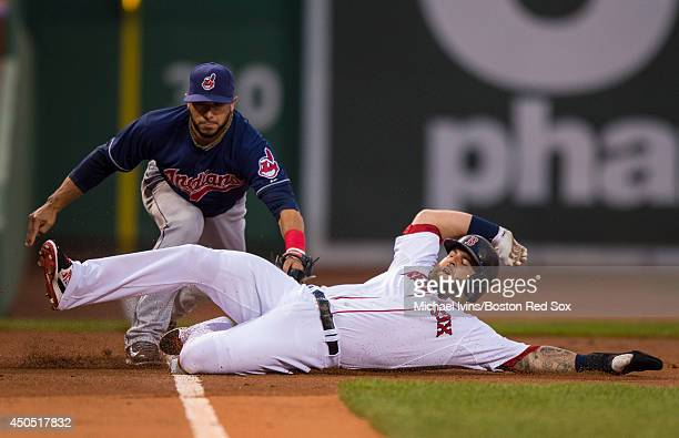 Mike Napoli of the Boston Red Sox slides underneath a tag by Mike Aviles of the Cleveland Indians after advancing to third base on a single by Daniel...