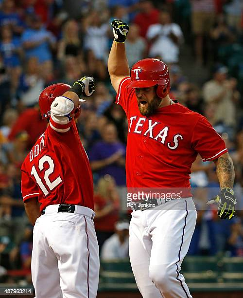 Mike Napoli of the Texas Rangers celebrates with teammate Rougned Odor after Napoli hit a solo home run in the second inning against the Oakland...