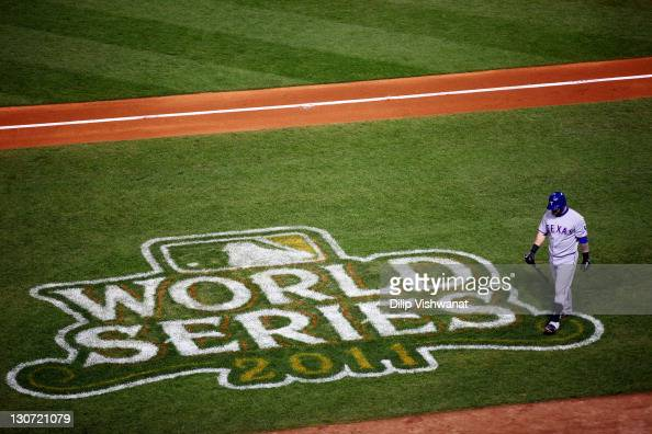 Mike Napoli of the Texas Rangers walks back to the dugout after striking out in the fourth inning during Game Seven of the MLB World Series against...