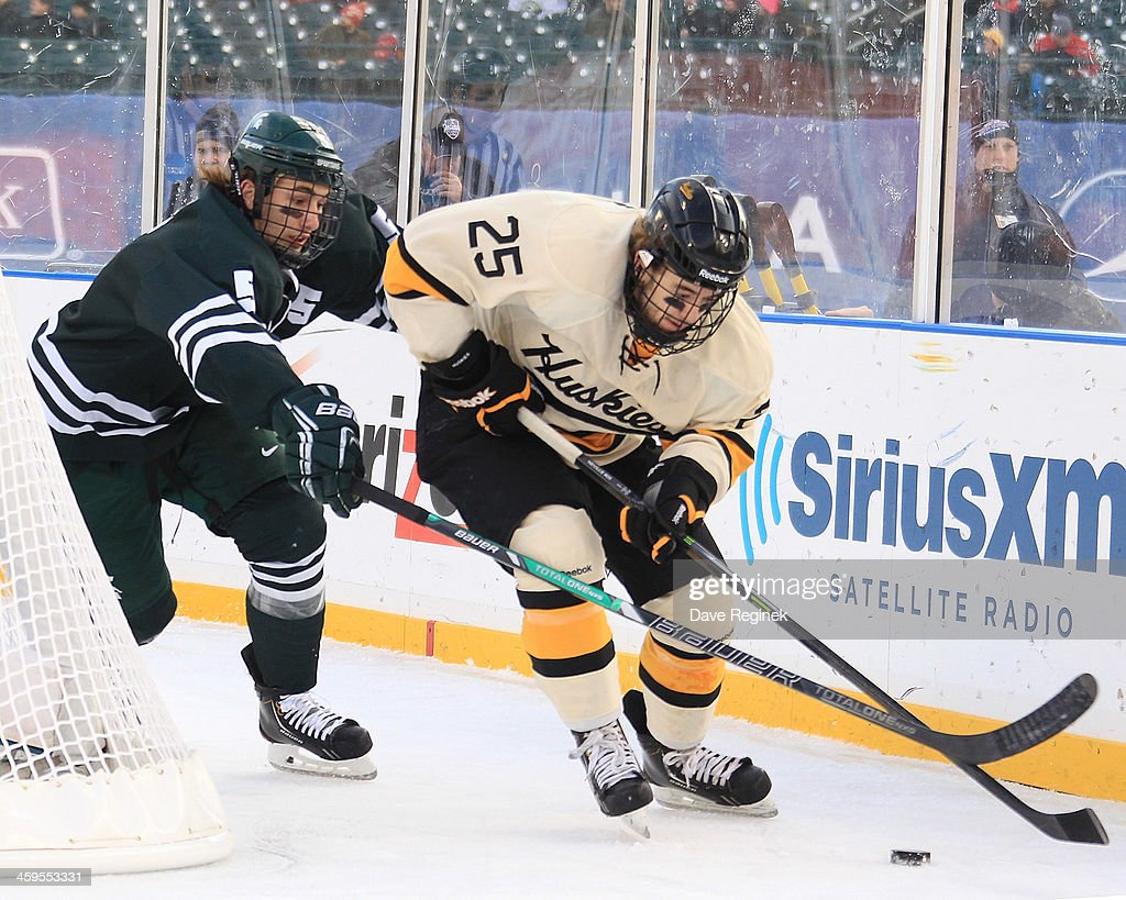 Mike Neville #25 of the Michigan Tech Huskies controls the puck in front of RJ Boyd #5 of Michigan State Spartans during game one of the Hockeytown Winter Festival Great Lakes Invitational - Day 1 played outdoors at Comerica Park on December 27, 2013 in Detroit, Michigan. The Huskies won in a shoot-out 3-2