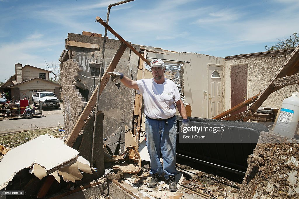 Mike Newbury cleans debris from his late father-in-law's home after it was destroyed when a tornado ripped through the area on May 22, 2013 in Moore, Oklahoma. Newbury had fixed the home up to prepare for it's sale before it was destroyed. The tornado of at least EF4 strength and two miles wide touched down May 20 killing at least 24 people and leaving behind extensive damage to homes and businesses. U.S. President Barack Obama promised federal aid to supplement state and local recovery efforts.