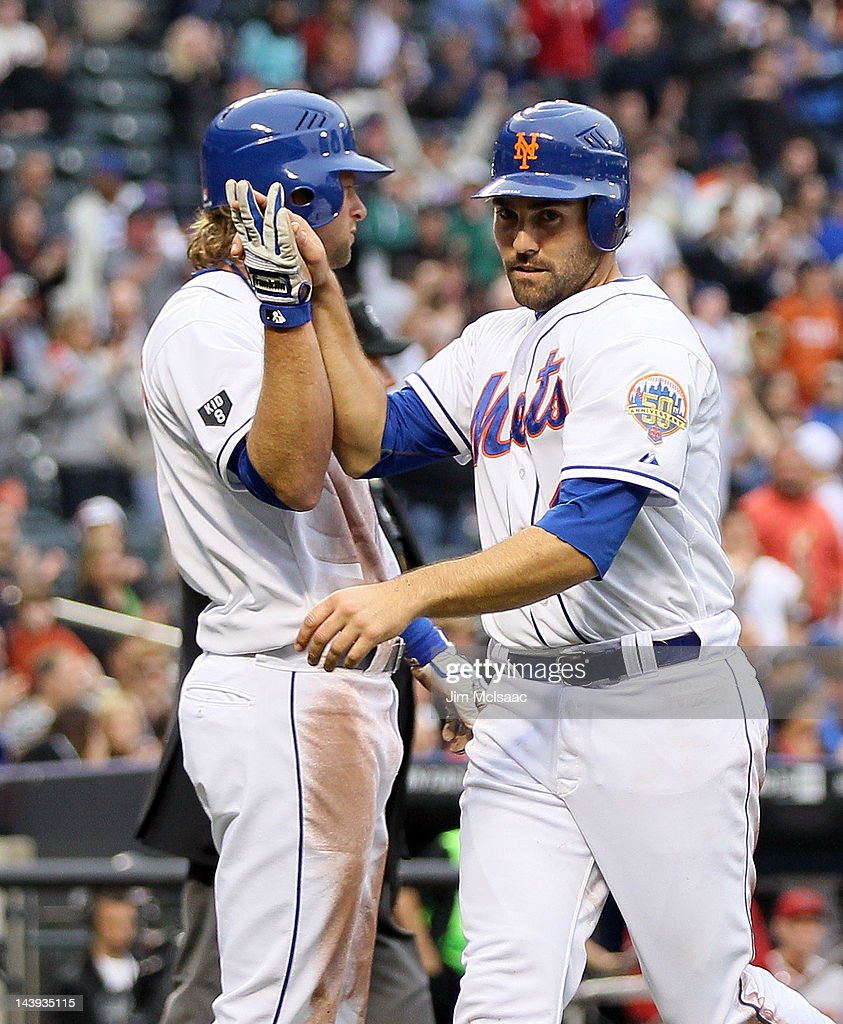 Mike Nickeas #4 and Kirk Nieuwenhuis #9 of the New York Mets celebrates scoring a fourth inning run against the Arizona Diamondbacks with his teammates in the dugout at Citi Field on May 5, 2012 in the Flushing neighborhood of the Queens borough of New York City.