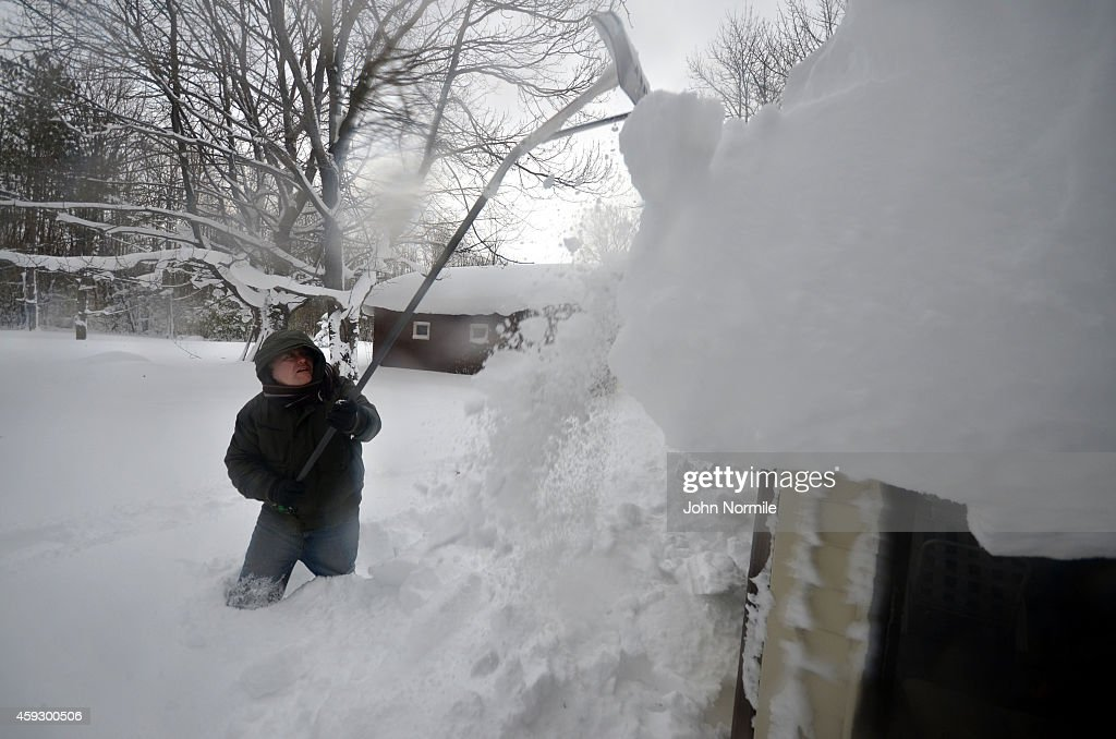 Mike Ostrander tries to remove some of the five feet of snow from his roof on November 20 2014 in the Lakeview neighborhood of Buffalo New York The...