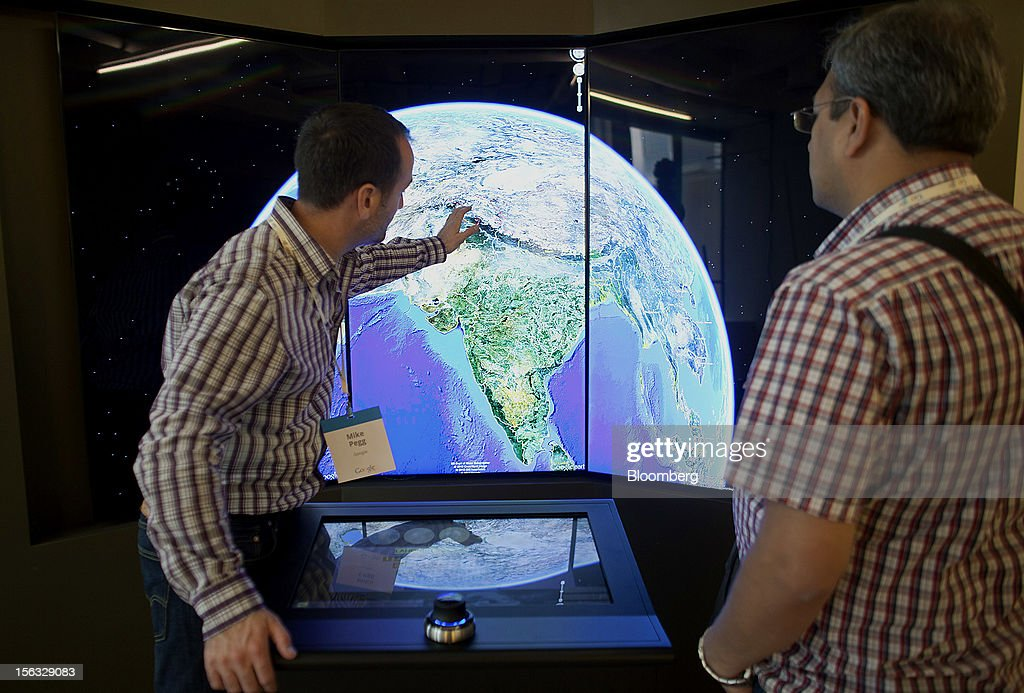 Mike Pegg, left, tries out 'Liquid Galaxy', a cluster of computers running Google Earth to create an immersive experience, during a media tour for the grand opening of Google Inc.'s new office in Toronto, Ontario, Canada, on Tuesday, Nov. 13, 2012. The office space encompasses five color-coded floors and features amenities such as a pool table, video games, mini-golf putting greens and a camping lounge where employees can hold meetings in a tent. Photographer: Brett Gunlock/Bloomberg via Getty Images