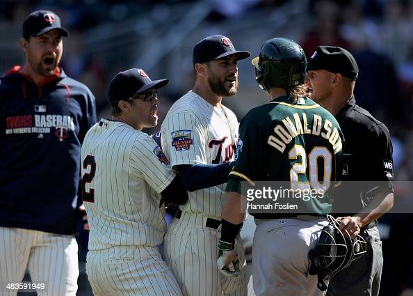 Mike Pelfrey Brian Dozier and Trevor Plouffe of the Minnesota Twins stop the progress of Josh Donaldson of the Oakland Athletics after Donaldson...