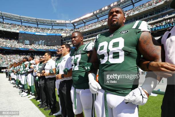 Mike Pennel of the New York Jets stands in unison with his teammates during the National Anthem prior to an NFL game against the Miami Dolphins at...