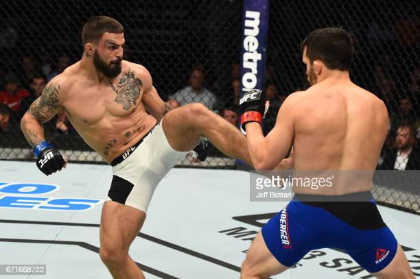 Mike Perry kicks Jake Ellenberger in their welterweight bout during the UFC Fight Night event at Bridgestone Arena on April 22 2017 in Nashville...