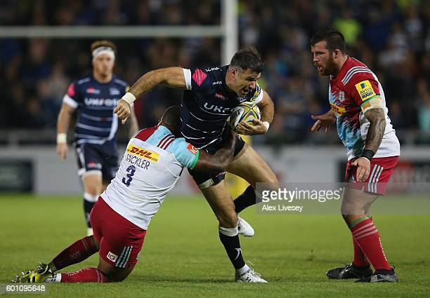 Mike Phillips of Sale Sharks is tackled by Kyle Sinckler of Harlequins during the Aviva Premiership match between Sale Sharks and Harlequins at AJ...