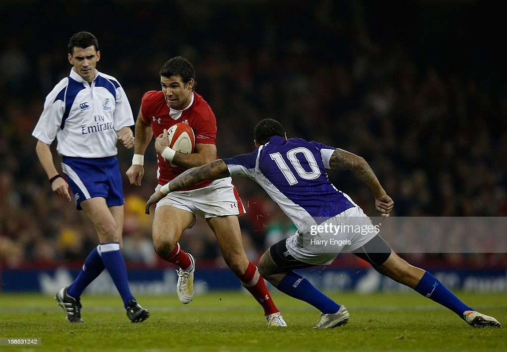 Mike Phillips of Wales avoids the tackle of Tusiata Pisi of Samoa as referee Pascal Gauzere looks on during the international match between Wales and Samoa at the Millennium Stadium on November 16, 2012 in Cardiff, Wales.