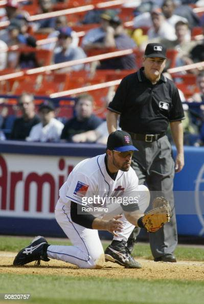 Mike Piazza of the New York Mets attempts to catch the ball as first base umpire Jerry Crawford watches during the game against the Montreal Expos at...
