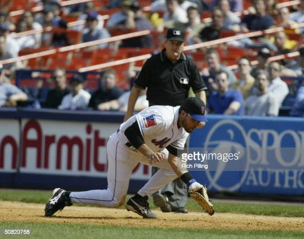 Mike Piazza of the New York Mets fails to catch the ball as first base umpire Jerry Crawford watches during the game against the Montreal Expos at...