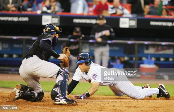 Mike Piazza of the New York Mets slides into home and scores off of a Cliff Floyd double as catcher Chris Snyder of the Arizona Diamondbacks misplays...