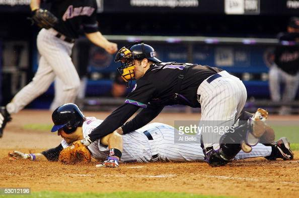 Mike Piazza of the New York Mets slides into home and scores off of a Cliff Floyd double as catcher Chris Snyder of the Arizona Diamondbacks applys...