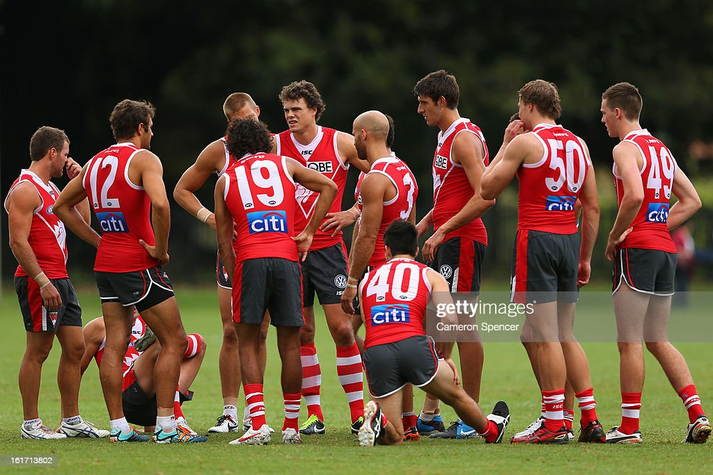 Mike Pike (C) of the Swans and team mates talk during an intra-club practice match during a Sydney Swans AFL training session at Moore Park on February 15, 2013 in Sydney, Australia.
