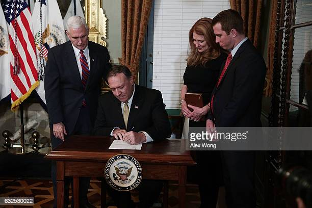 Mike Pompeo signs the affidavit of appointment as his wife Susan Pompeo son Nick Pompeo and US Vice President Mike Pence look on during a swearing in...