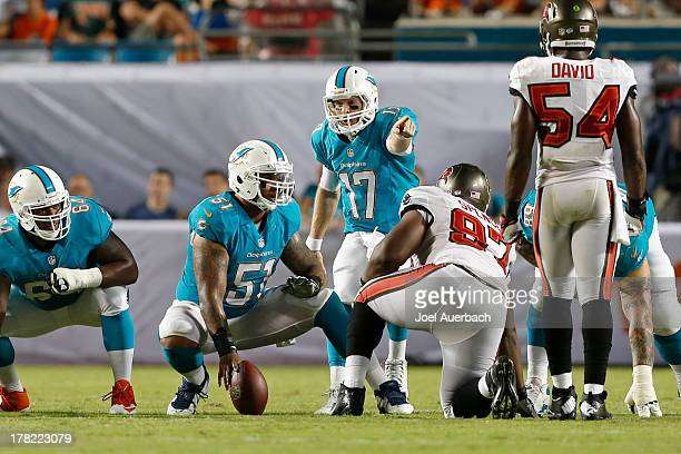 Mike Pouncey looks back as Ryan Tannehill of the Miami Dolphins calls an audible against the Tampa Bay Buccaneers during a preseason game on August...