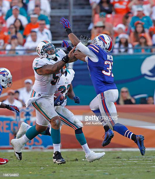 Mike Pouncey of the Miami Dolphins and George Wilson of the Buffalo Bills battle along the line on December 23 2012 at Sun Life Stadium in Miami...