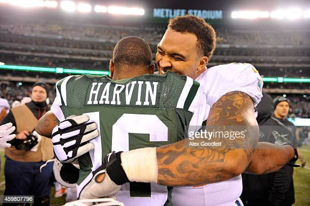Mike Pouncey of the Miami Dolphins hugs Percy Harvin of the New York Jets after their game at MetLife Stadium on December 1 2014 in East Rutherford...