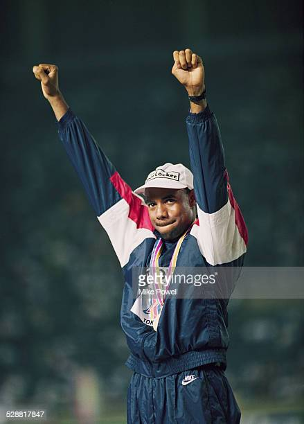 Mike Powell of the United State celebrates on the podium after making his world record leap during the Long Jump event at the IAAF World Athletic...