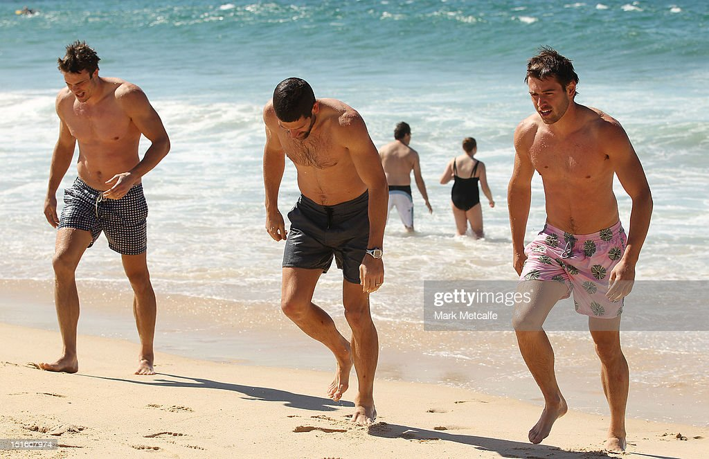 Mike Pyke, Martin Mattner and Nick Smith of the Swans walk out of the ocean during a Sydney Swans media session at Coogee Beach on September 9, 2012 in Sydney, Australia.