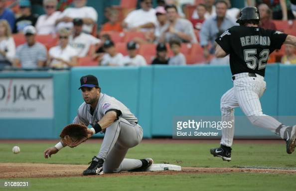 Mike Redmond of the Florida Marlins tries to beat the throw at first base as Mike Piazza of the New York Mets reaches to grab a low thrown ball...