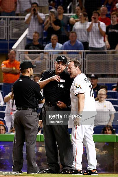 Mike Redmond of the Miami Marlins argues a call with umpires Mike Winters and Mark Wegner review a call during the eighth inning of the game between...